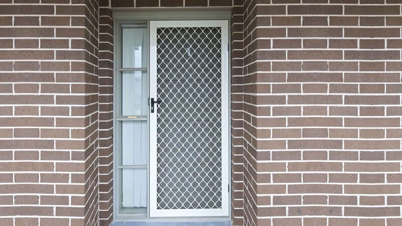 A hinged diamond grille screen door in white