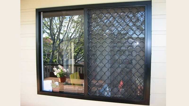 A sliding window with black diamond grille screen
